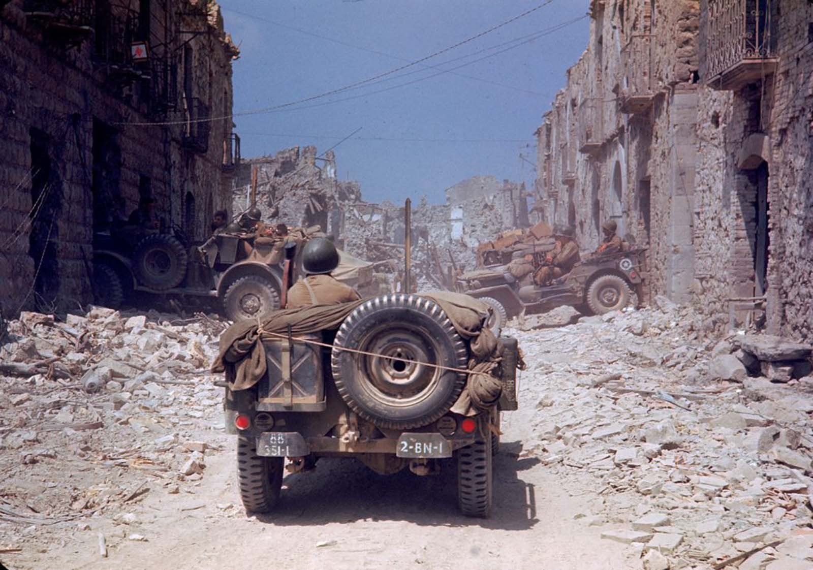 American jeeps traveled through a bombed-out town during the drive towards Rome, World War II.