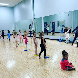preschoolers dance on colorful circles placed on a wooden floor in a room with mirrors at Arena Dance Academy