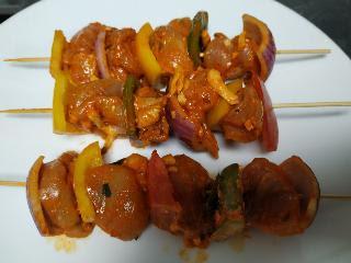 Threading chicken in wooden sticks for making chicken kebab on tawa