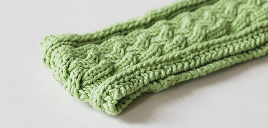 Light green hand-knit cabled headband resting flat on a white background.