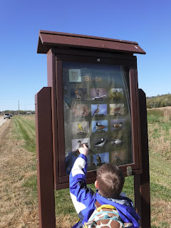 a boy points at a sign featuring pictures of animals at Prairie Park in Sioux City