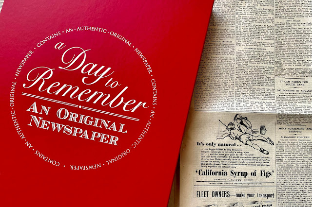 """A red classic gift box with """"a day to remember and original newspaper"""" next to an authentic newspaper"""