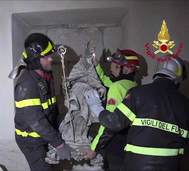 Os bombeiros italianos no momento que removem a imagem da cripta em ruínas