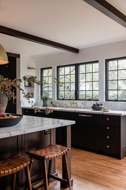 Black cabinetry kitchen with white marble countertops and backsplash around the sink windows in an East Sacramento home, Sacramento, California