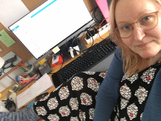 Silmälasipäinen nainen istuu tietokoneen äärellä mustapohjainen, valko-oranssikuvioinen yöpaita päällä ja villasukat jaloissa.