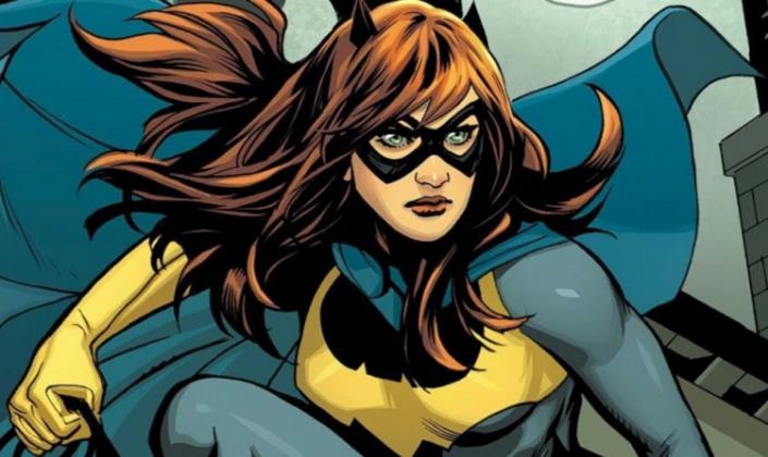 Imagem de capa: a Batgirl, uma mulher branca e ruiva com uma máscara de morcego que cobre a parte de cima do seu rosto, um traje cinza com uma capa azul, luvas amarelas e um morcego em seu peito com a mesma cor.