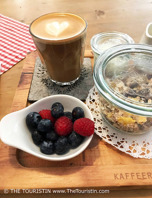 A cup of coffee, muesli in a glass, a small bowl of raspberries and blueberries on a wooden table with a red and white checkered table cloth.