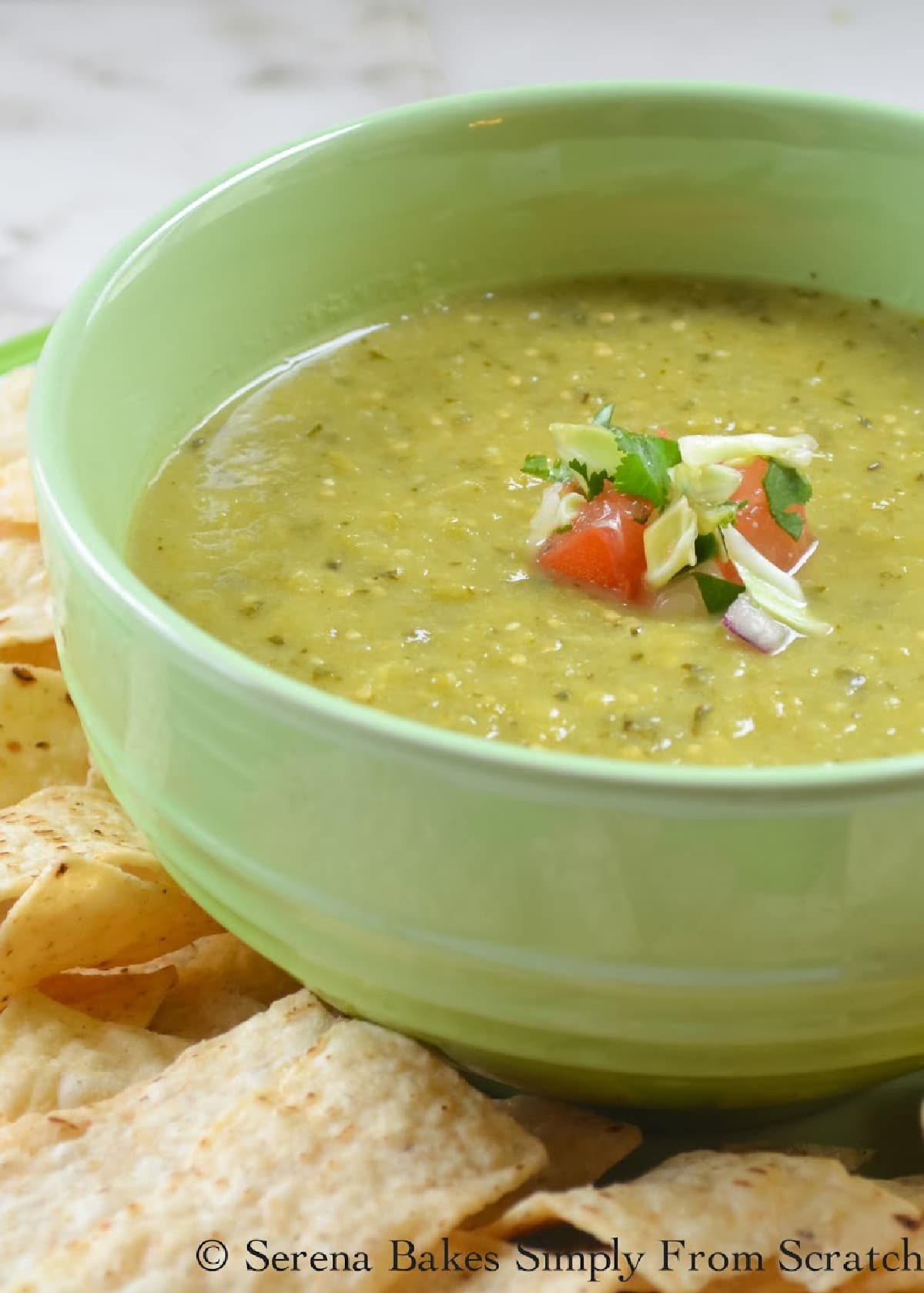 Tomatillo Salsa Verde Recipe in a green bowl with chips on the side.