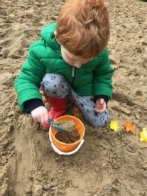 A little boy making sandcastles