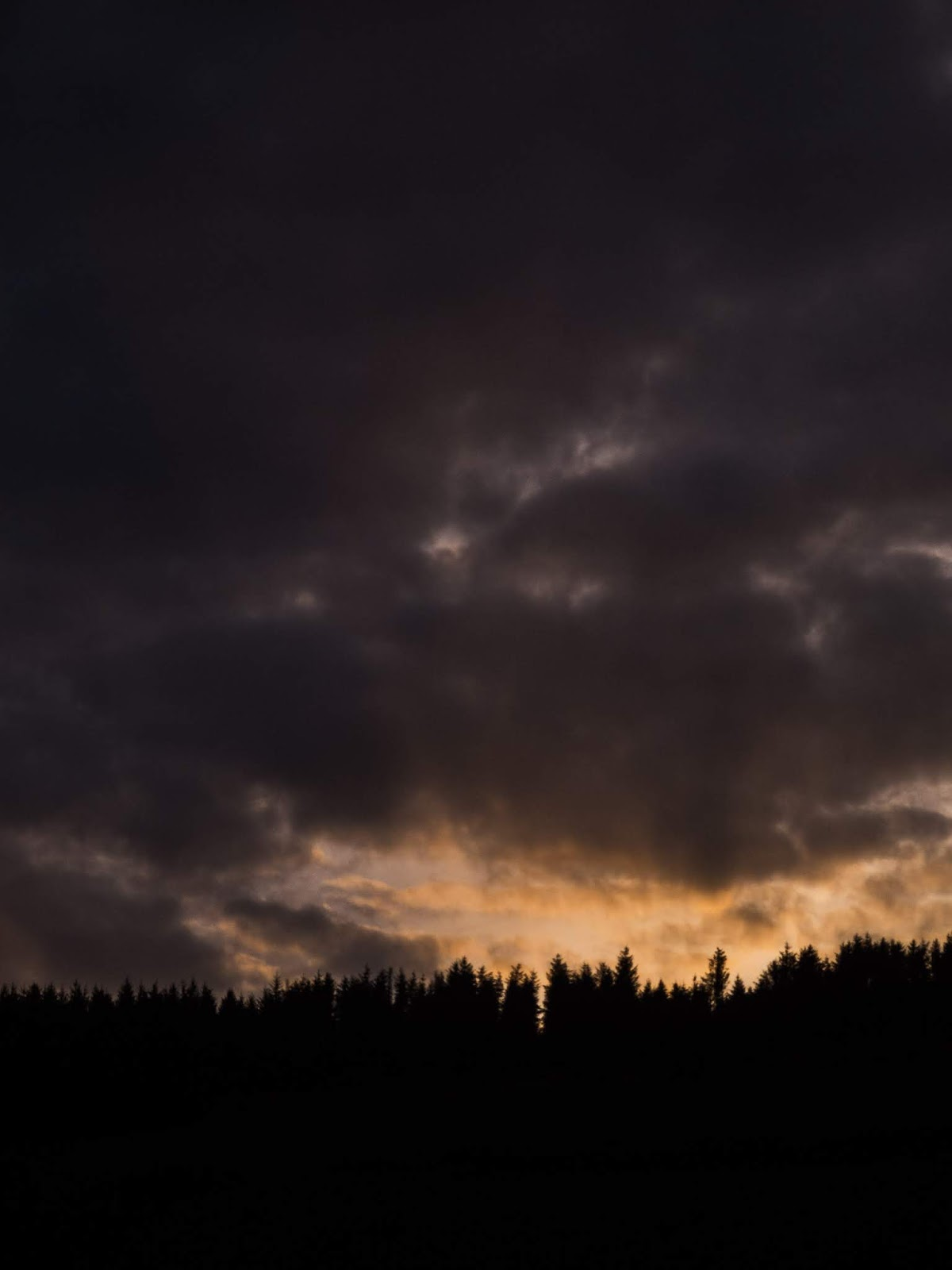 Sun rays coming up over a mountain surrounded by dark clouds in Co.Cork, Ireland.