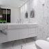 Banheiro com piso, parede e bancada revestidos com porcelanato marmorizado!
