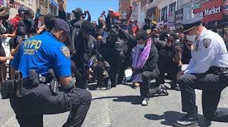 ضباط شرطة يركعون للصلاة مع متظاهرين محتجين على مقتل جورج فلويد