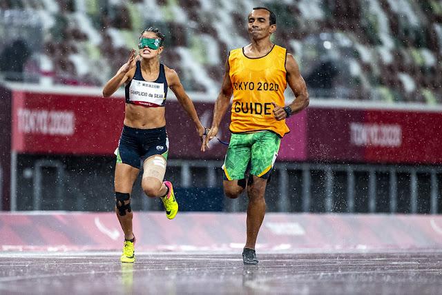 Thalita, a esquerda, e o guia, à direita, cruzam a linha de chegada na prova debaixo de uma forte chuva
