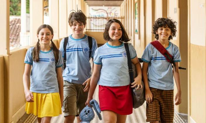 Imagem de capa: os personagens da direita para a esquerda, Magali, Cebolinha, Mônica e Cascão, interpretados pelos atores-mirins em live-action, com uniformes de escola, mas com detalhes que lembram as suas roupas dos quadrinhos, Magali usa uma saia amarela, Mônica usa uma saia vermelha e segura o Sansão e os quatro estão em um corredor de escola.