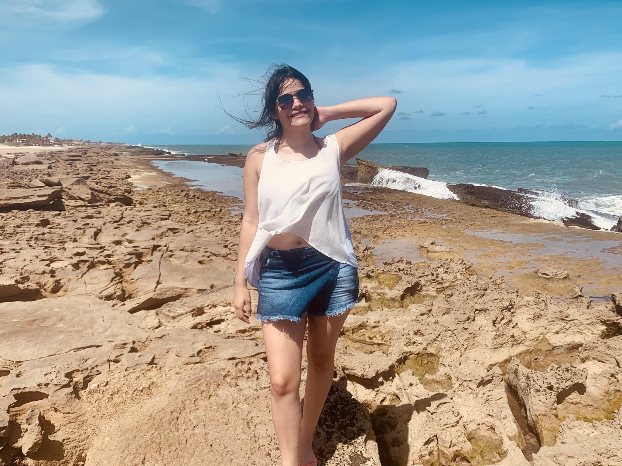 mulher em cima de pedras em uma praia