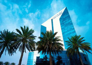 Source: Dubai Chamber of Commerce and Industry. View of building in Dubai with palms in foreground.
