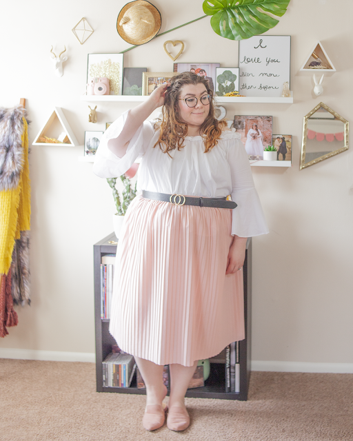 An outfit consisting of a white ruffled off the shoulder blouse with bell sleeves tucked into a pink pleated midi skirt and muted pink pointed mules.