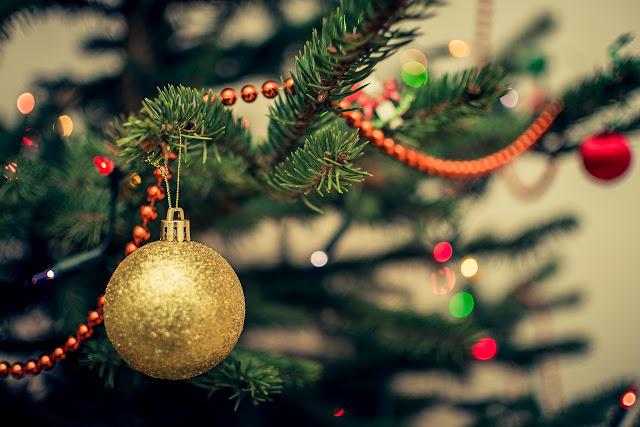 yellow glittery bauble on christmas tree