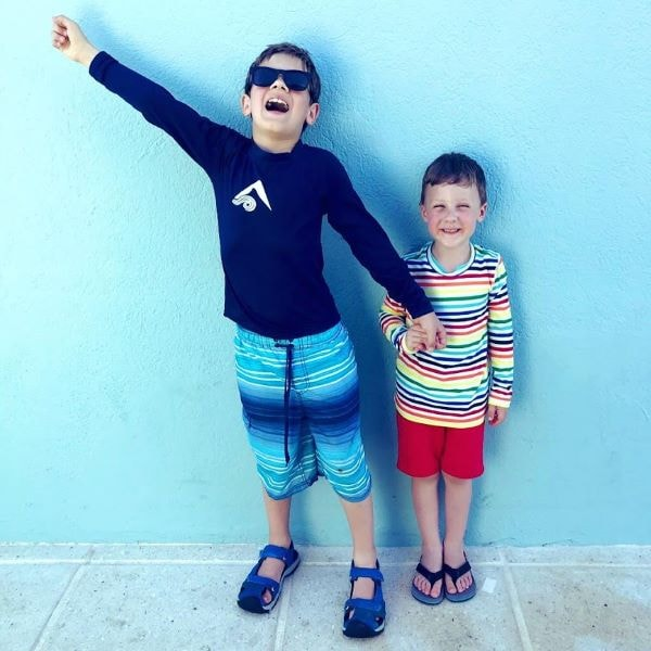 Kids in rash guards and swimming gear