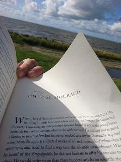 Aufgeschlagenes Buch über die Diderot-Enzyklopädie. Im Hintergrund Badestelle Wesselburenerkoog und Nordsee.