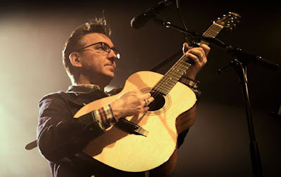 Richard Hawley on stage playing a guitar.