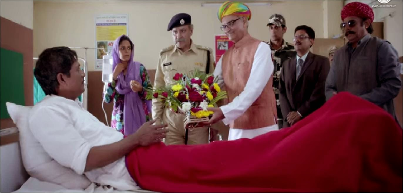 Mona Singh starer Zed Plus movie trailer still featuring Adil Hussain on hospital bed, receiving flower bouquet