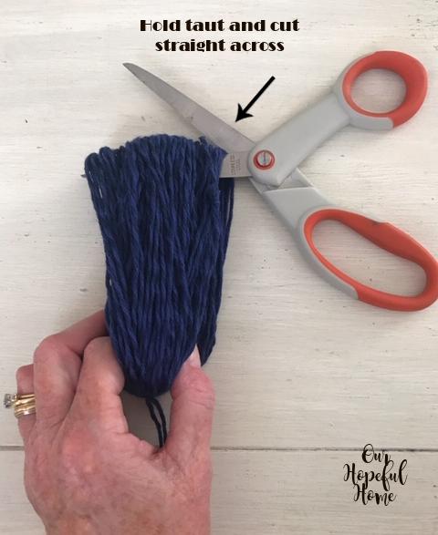 tassel yarn being cut with orange scissors