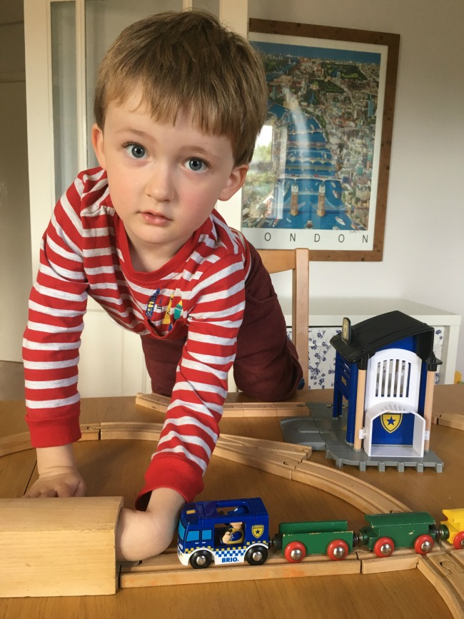 Boy-putting-hand-in-brio-tunnel-searching-for-something-with-police-car-and-other-trains-attached