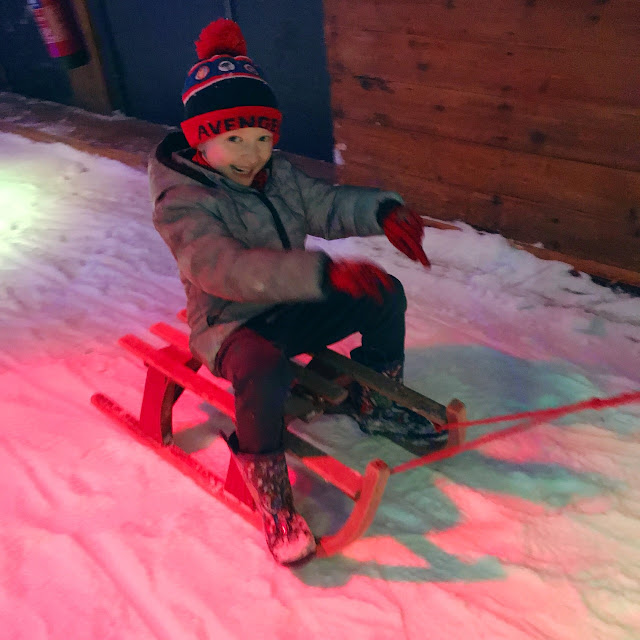 Little boy being pulled on a wooden sledge in the snow as he smiles