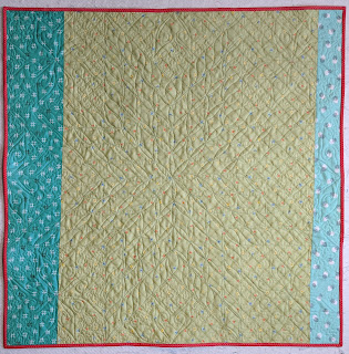 Light green print with aqua prints to each side create the quilt back