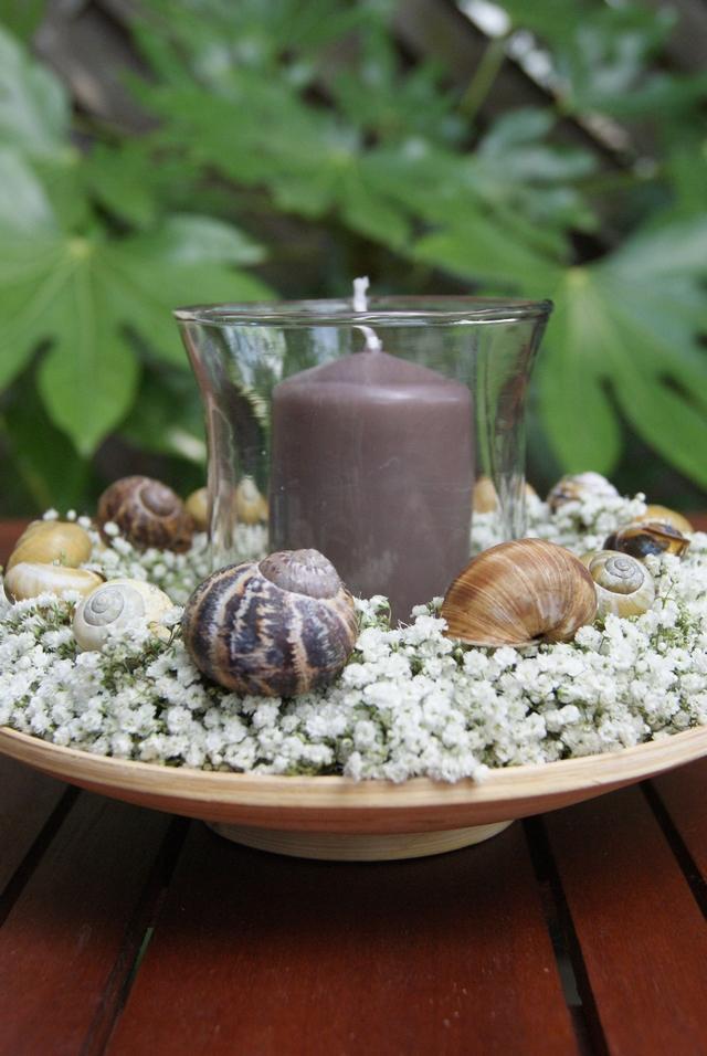 Sommerliche Tischdeko mit Windlicht auf Holzteller und Schleierkrautkranz