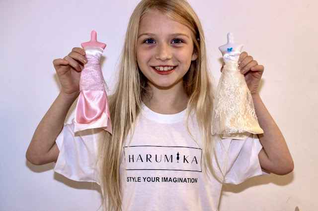2 long elegant dresses made with the Harumika Bridal Gown set being held by a child wearing a white t-shirt which says Harumika Styling Your imagination