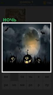на фоне луны светятся тыквы и летают летучие мыши