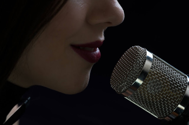 Singer in front of a microphone. Isolated on a dark background