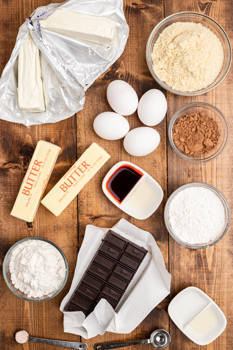 Overhead photo of the ingredients needed to make Keto Red Velvet Cheesecake Brownies on a wooden table.