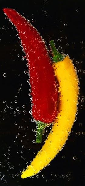 خلفية ثمار الفلفل الحار الاحمر و الاصفر في سائل اسود