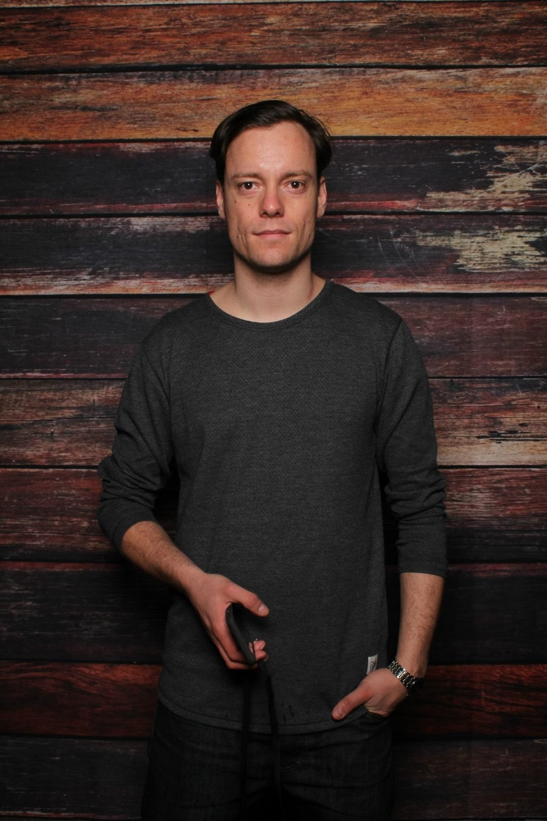 Image shows Martin Kleppe looking straight ahead at the camera. He is standing against a wooden wall