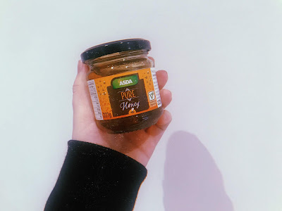 my left hand holding a jar of honey