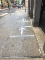 Arrows on the sidewalk for social distancing outside Starbucks