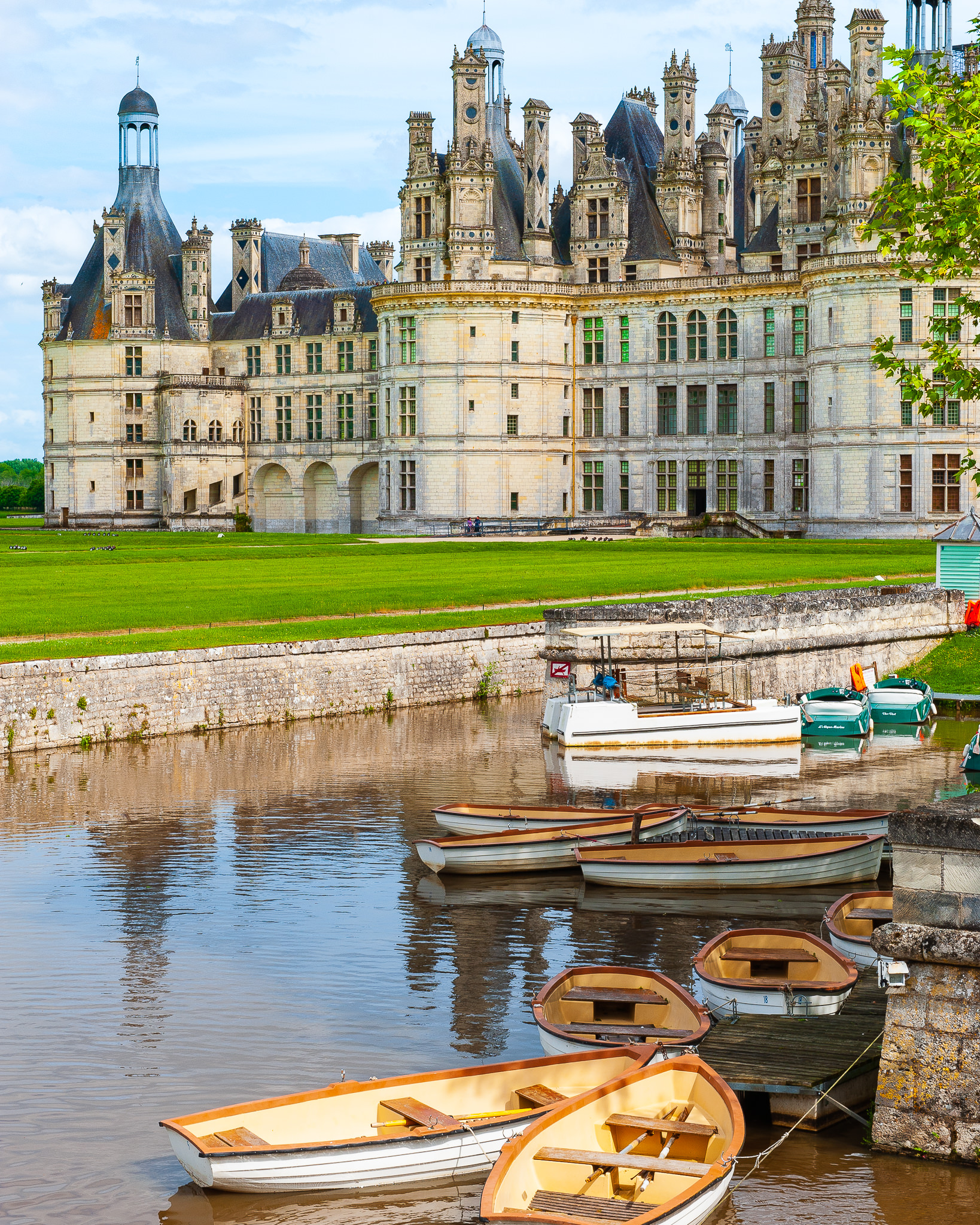 a photo of boats moored at the chateau de chambord loire valley on a sunny day