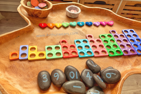 natural wooden tuff tray with needle felt hearts, numicon, number stones and painted wooden discs