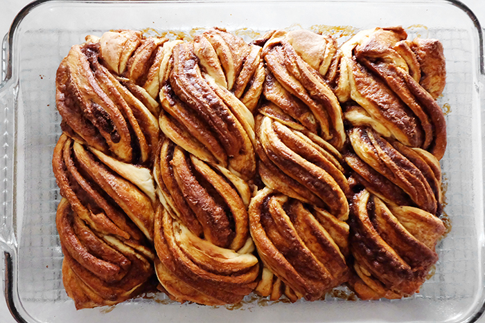 freshly baked twisty cinnamon rolls in pan