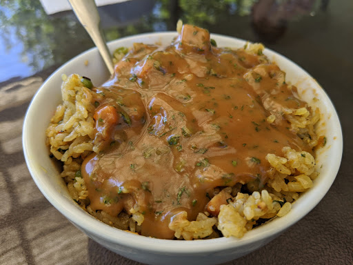 A bowl of fried rice covered with a rich, cilantro peanut butter sauce