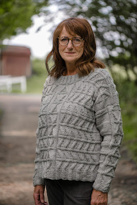 Photo of model wearing a hand knitted cable sweater