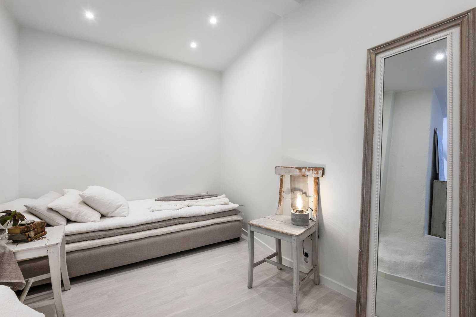 dormitorio blanco estilo nordico cama mesita auxiliar lino libros viejos vintage