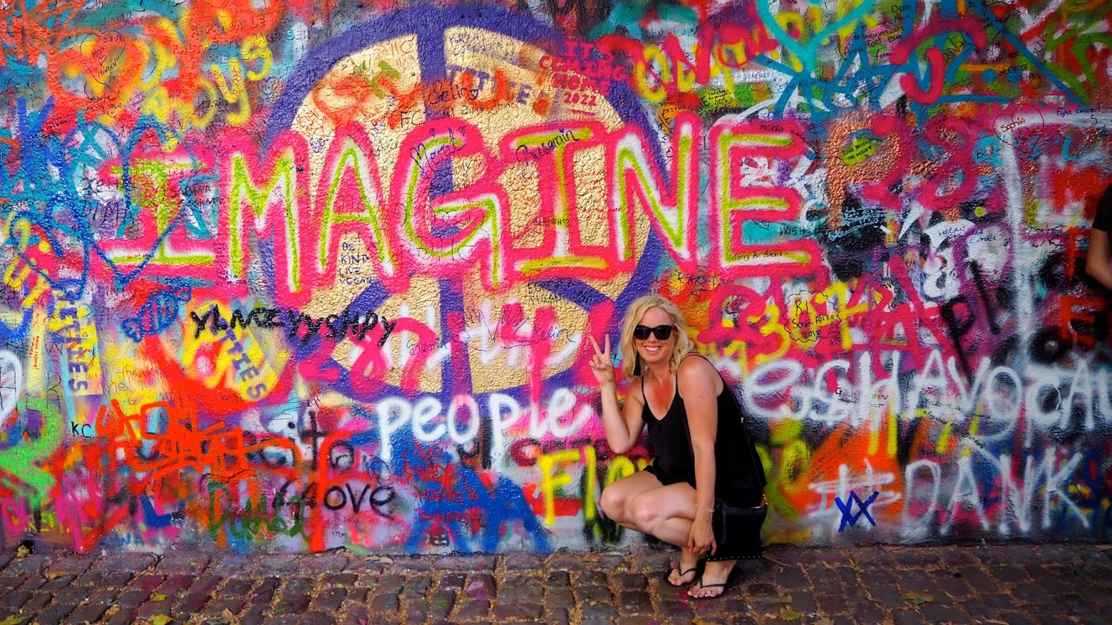 "Ashley Turner sitting in front of John Lennon graphiti wall in Prague which says ""Imagine"" making a peace sign"