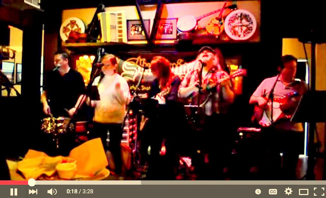 left to right, drummer, lead singer, 3 string players in bar scene record the song