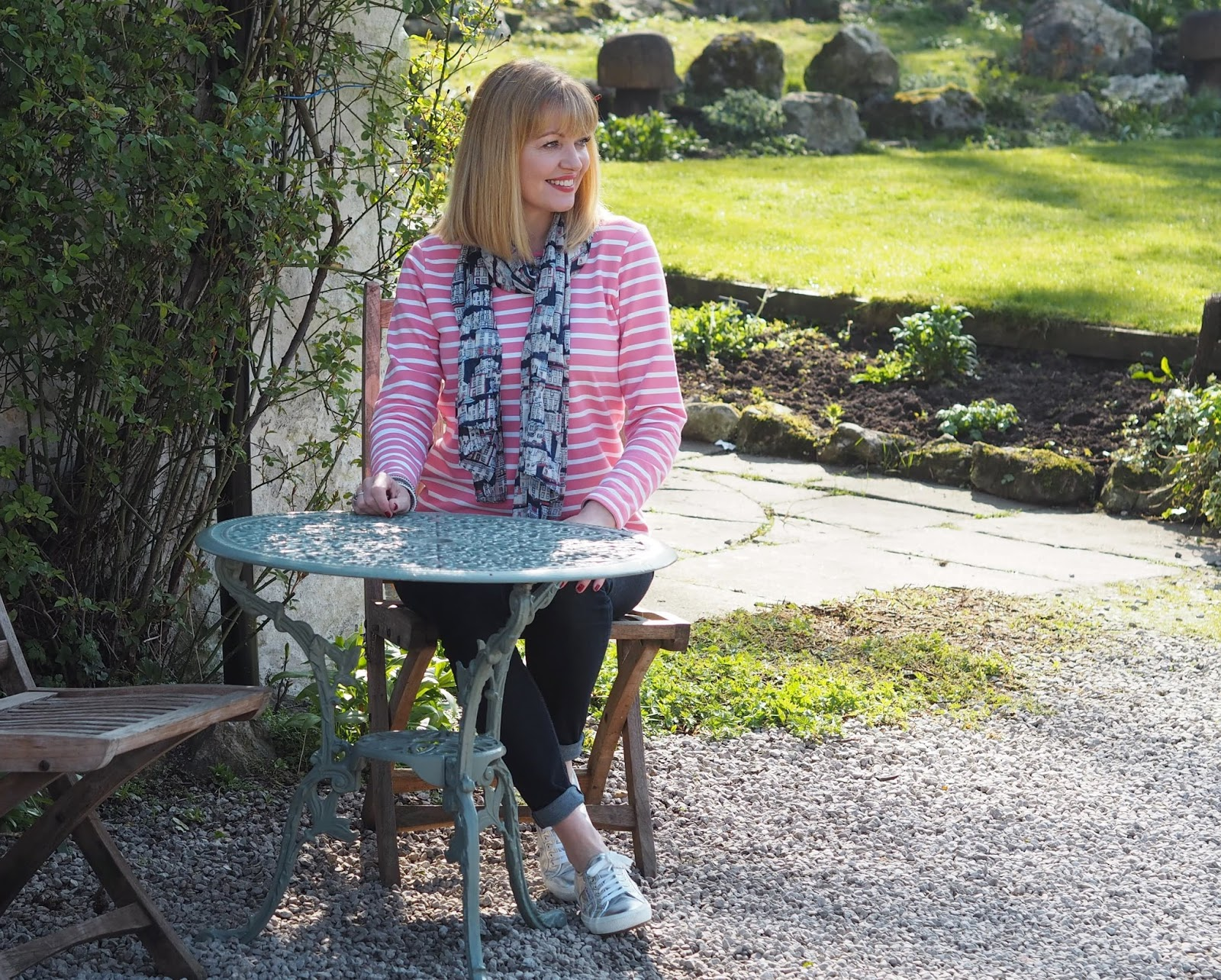 pink and white striped breton top by Tulchan with skinny jeans and silver Superga pumps, seated at an outdoor table