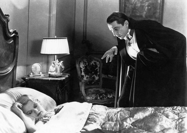 Bela Lugosi as Dracula looming over woman in bed
