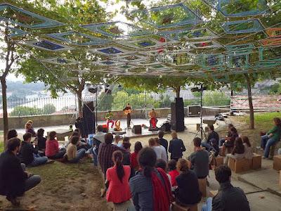 Concerto ao ar livre e pessoas sentadas na relva